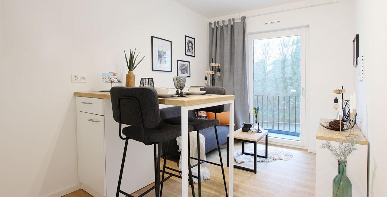 In den 2-Zimmer-Wohnungen der Kategorie Large ist der Wohn- und Essbereich vom Schlafzimmer getrennt. Ein Esstisch mit Barstühlen, ein Sofa mit Couchtisch sowie intelligente Stauraumlösungen sorgen für hohen Wohnkomfort.