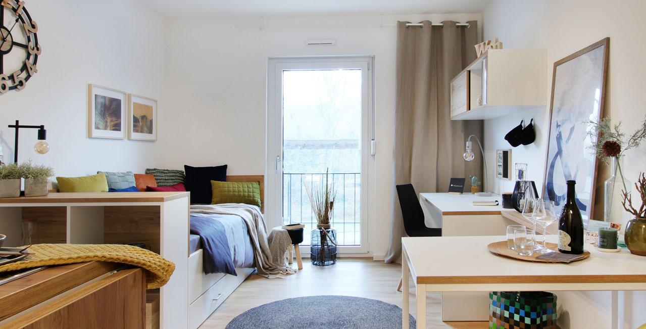 Küche, Arbeitsplatz, Tisch, Regalelement und ein Bett, das gleichzeitig Sofa ist – die 1-Zimmer-Wohnung der Kategorie Small hat alles, was man braucht